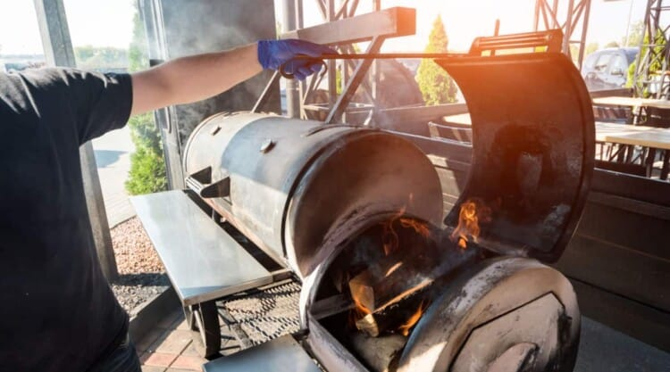 Large bbq smoker with fire box held open by a man with a gloved hand