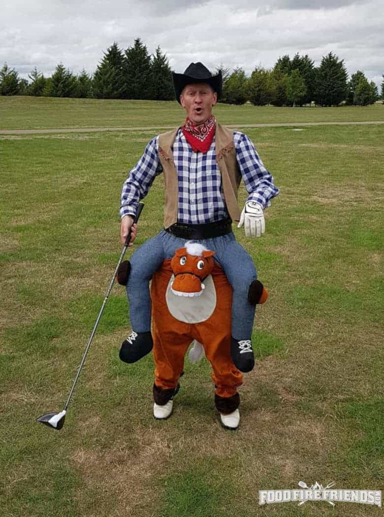 Man riding a fancy dress horse while holding a golf club