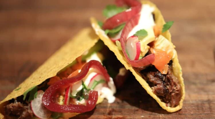 2 beef cheek tacos with onion, cheese, soured cream, coriander