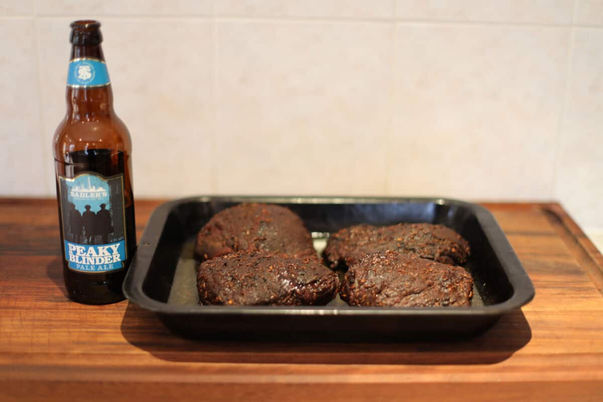 Four beef cheeks in a pan next to a bottle of IPA