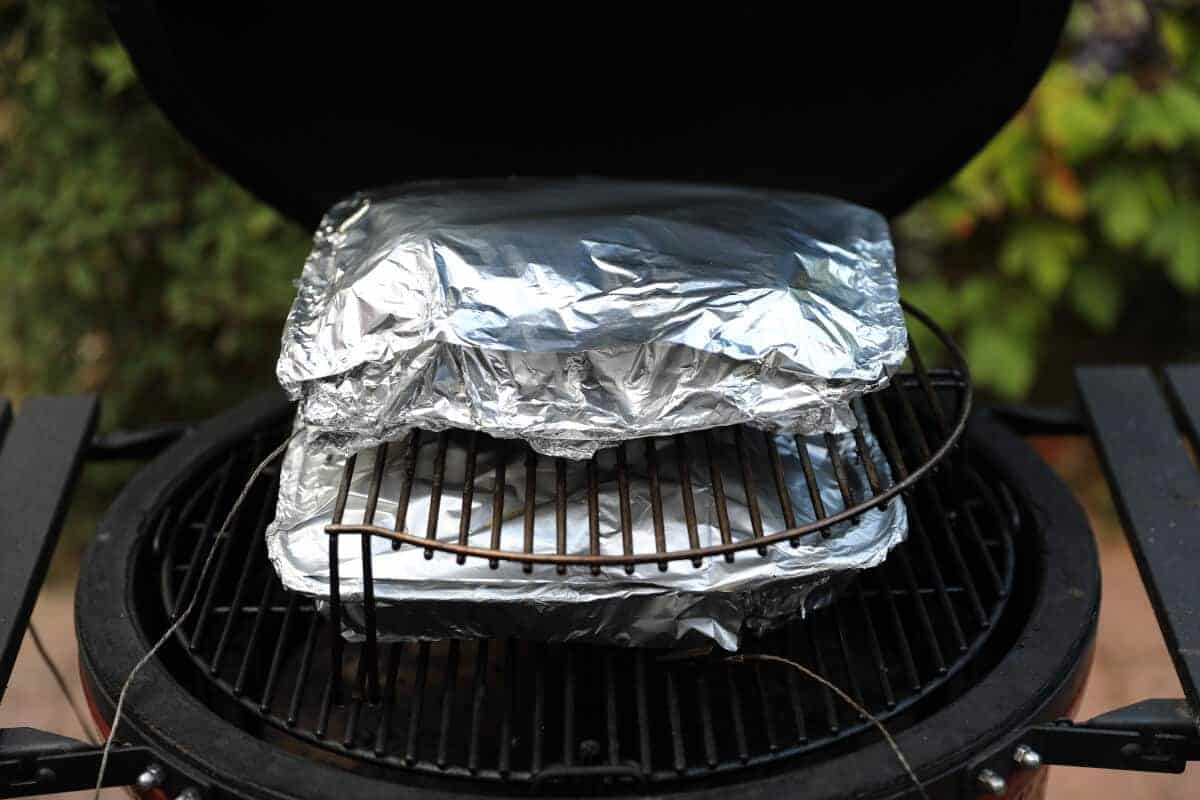 Beef ribs wrapped in aluminum foil on a kamado joe smoker
