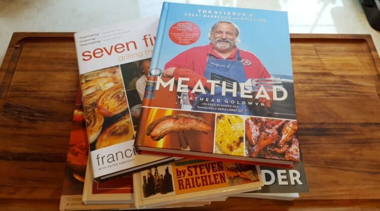 Some of the best bbq and grilling cookbooks piled on each other on a table
