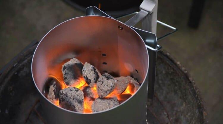 A charcoal chimney starter half full of hot burning coals