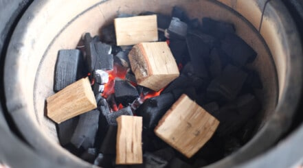 Close up of a Kamado Joe fire bowl filled with lump charcoal and smoking wood