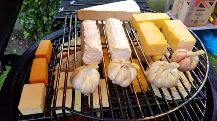 Cold smoke generator being used inside of a kamado grill to smoke cheeses and garlic