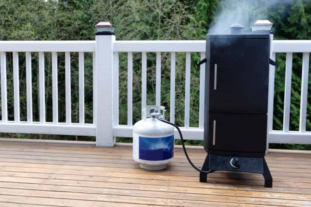 a propane gas smoker on a wooden balcony with LP tank beside it