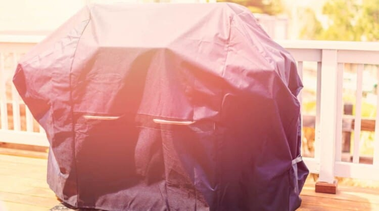 A grill cover in bright sunlight on a wooden deck