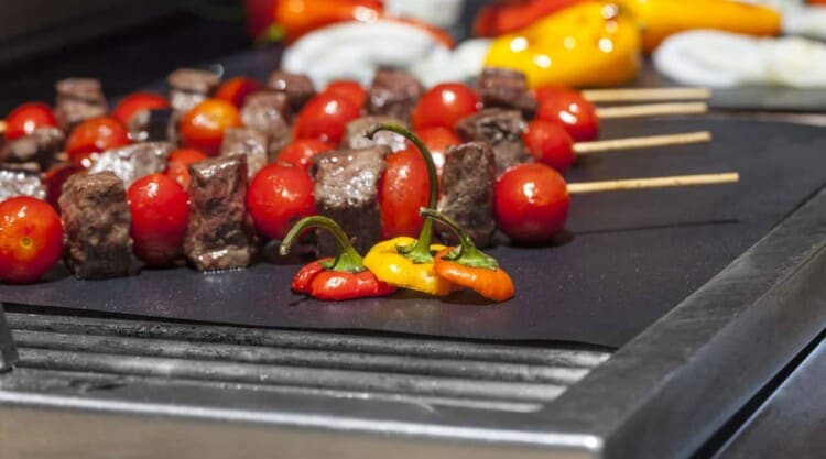 Close up of some mixed meat and veg kebobs on a grill mat