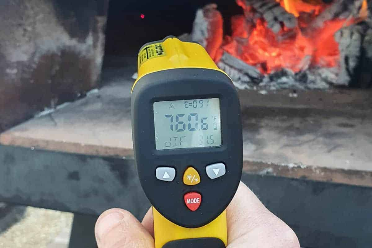 No touch infrared thermometer taking the temperature of a pizza oven.
