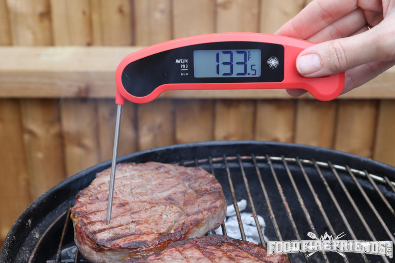 An instant read thermometer taking the reading of a steak on a grill