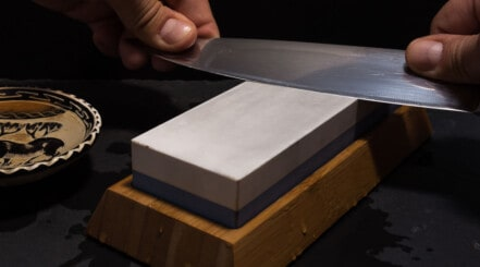 Kitchen knife being sharpened on a whetstone