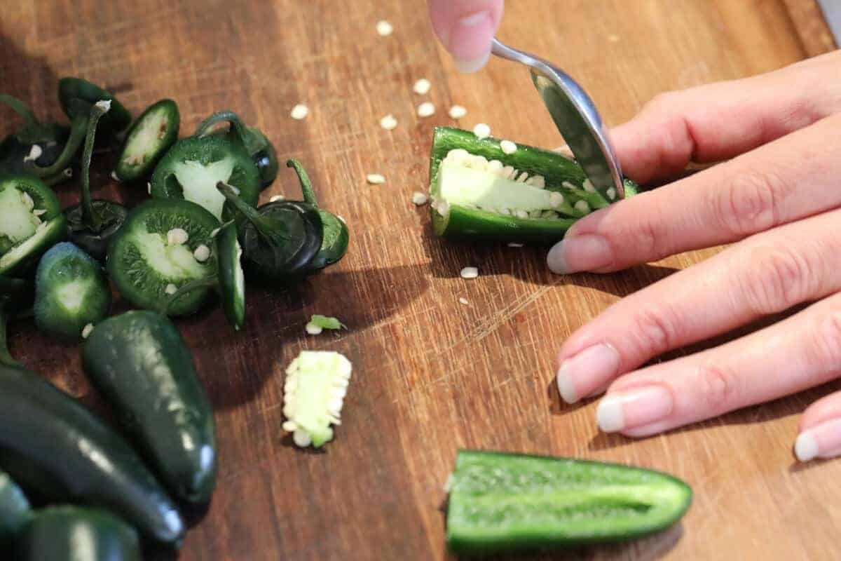 deseeding halved jalapenos with a teaspoon