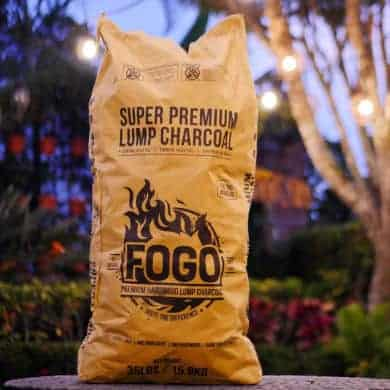 Bag of fogo lump charcoal with a garden background at dusk
