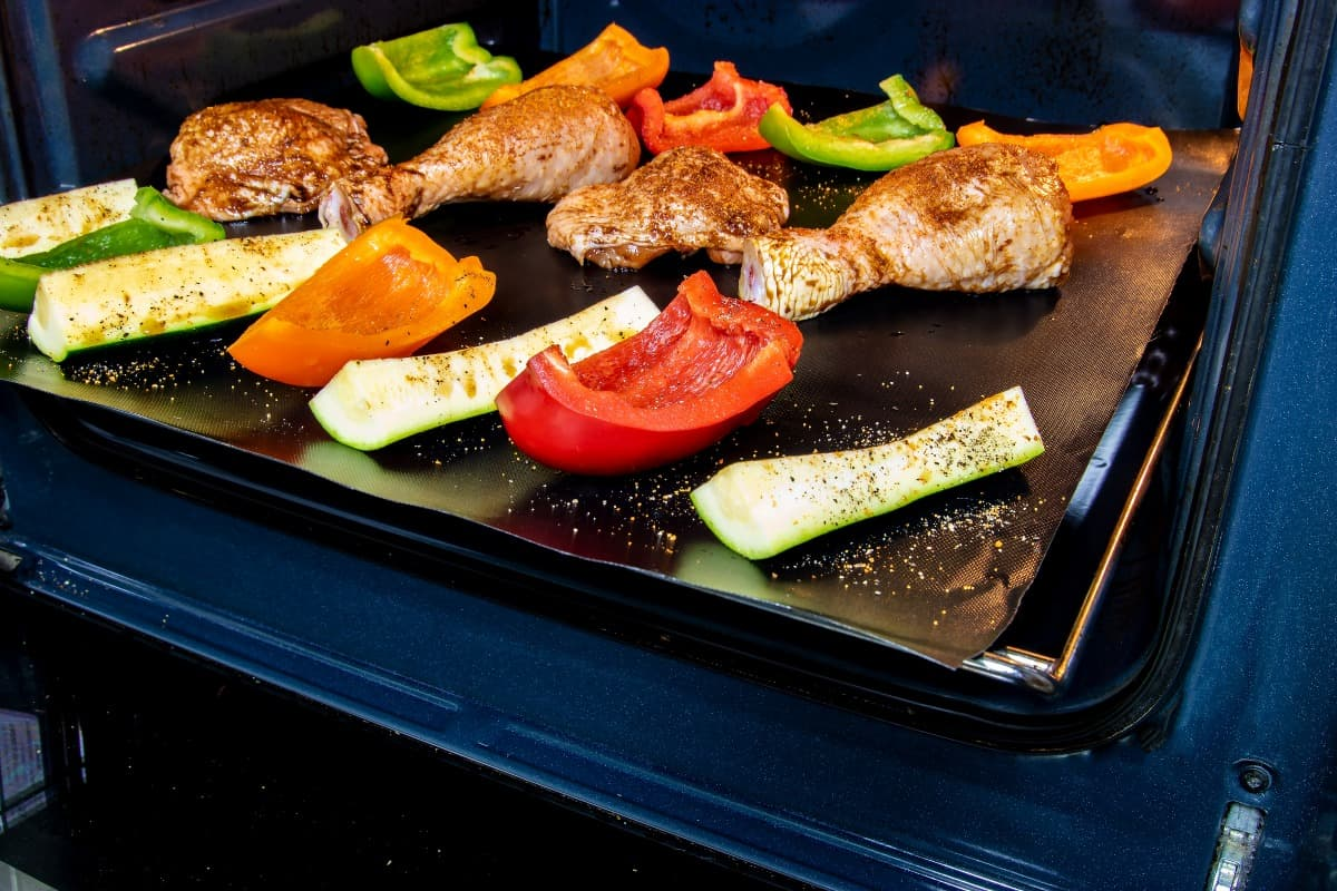 A grill mat being used in an oven to grill vegetables