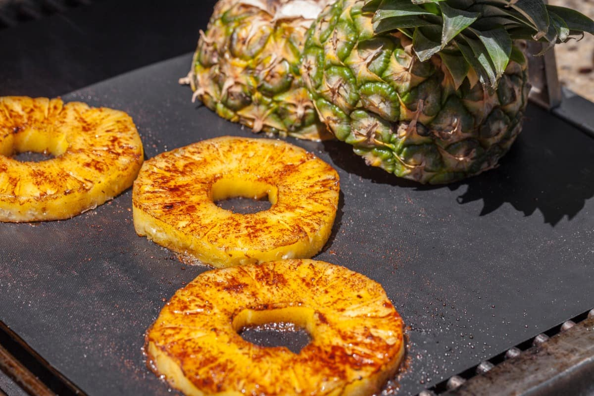 Pineapple slices, and the top half of a pineapple on a hot grill mat