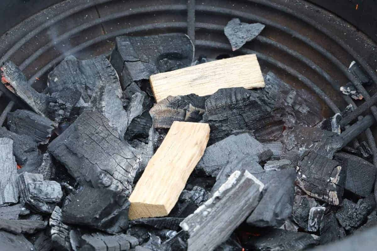 2 chunks of applewood atop smoldering lump charcoal in a kamado joe
