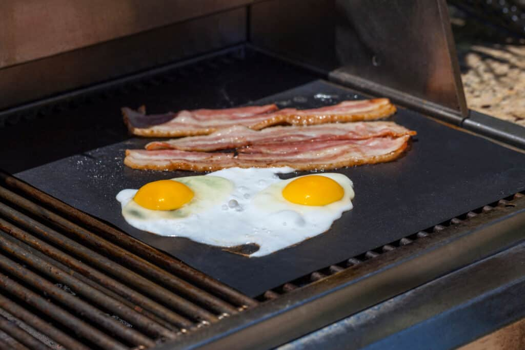 Eggs and bacon being cooked on a grill mat