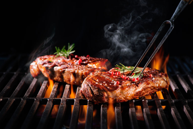 2 steaks being flame grilled on a gas grill, isolated on black
