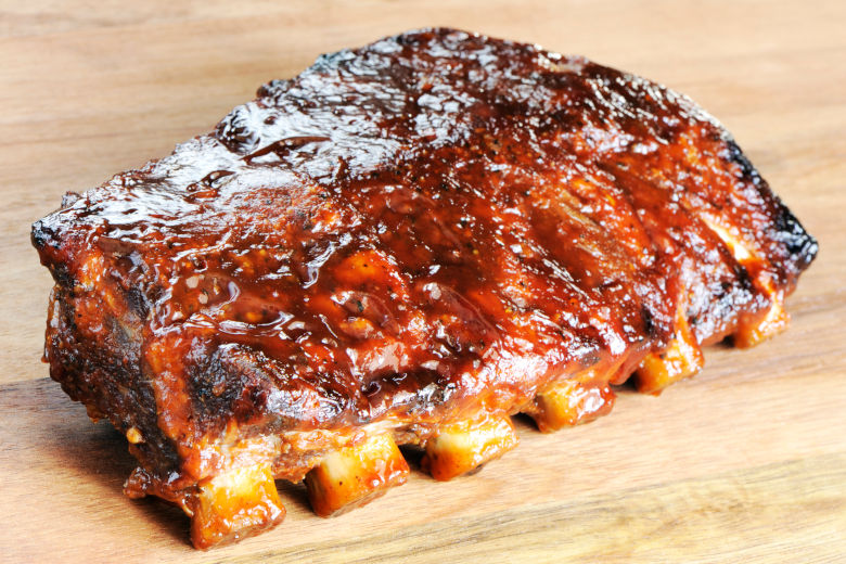 Grilled barbecue ribs covered in sauce, on a wooden background