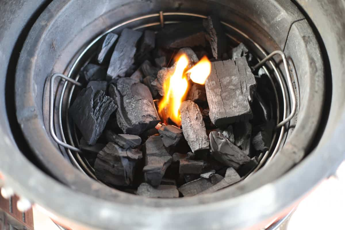 Kick ash basket in a kamado grill, full of coals with the center lit