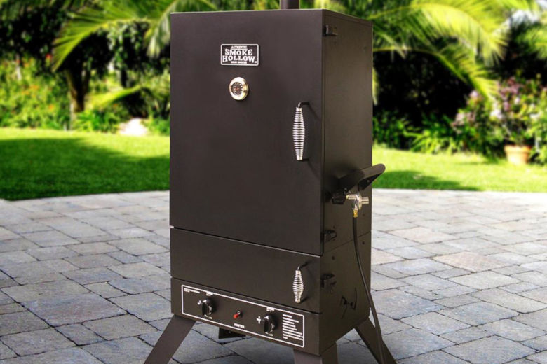 Smoke Hollow gas smoker on a patio with grass garden in background
