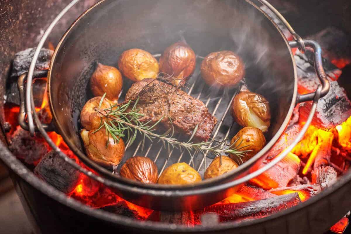 Beef, rosemary and roast potatoes in a dutch oven on a grill