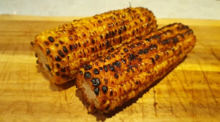 2 grilled corn on the cob without husks, sitting on a wooden board