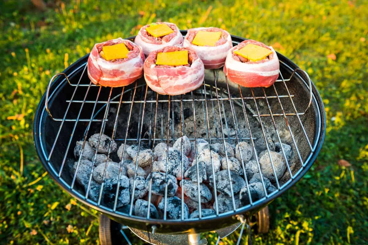 Beer can burgers, wrapped in bacon, being grilled indirect with charcoal