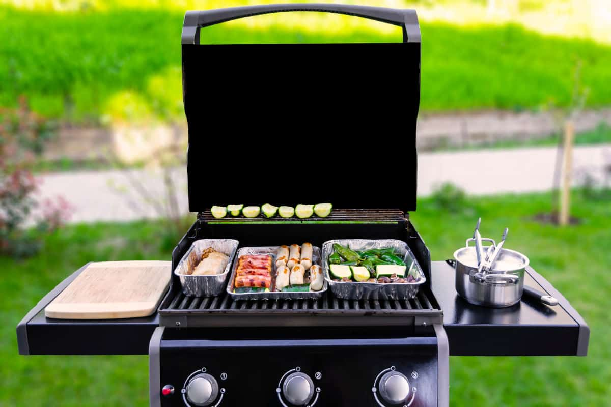 Gas grill, lid open, food on grates and a pan on a side burner