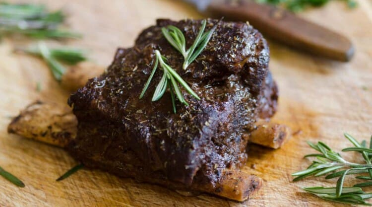 Beef ribs on a cutting board with a few rosemary leaves