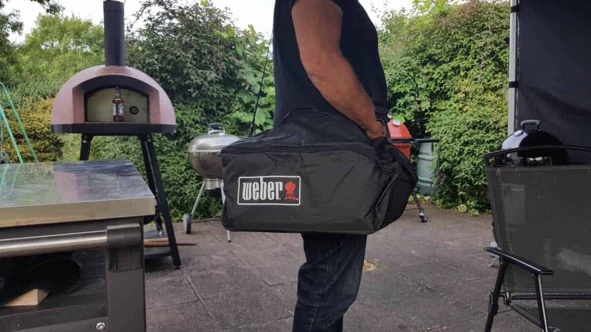 A man carrying the weber GA in it's purpose bag from Weber
