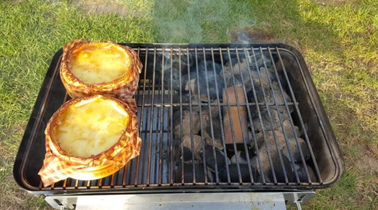 Two camembert cheeses being smoked on a weber go anywhere charcoal grill