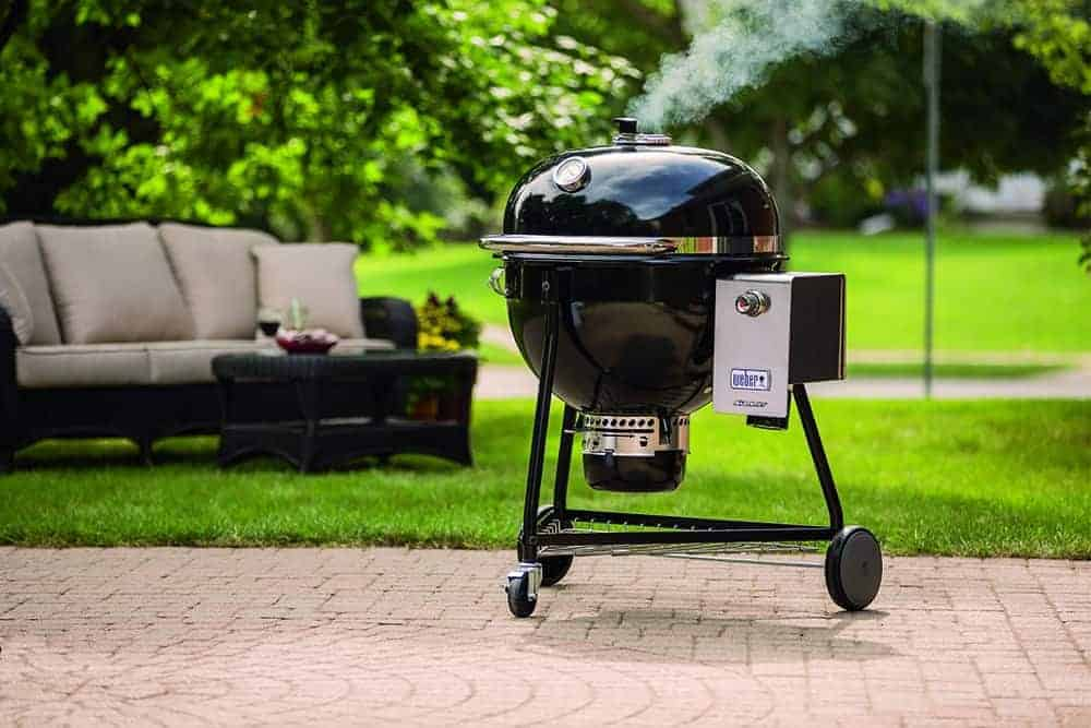 Weber summit charcoal grill on patio, near grass garden with sofa in background