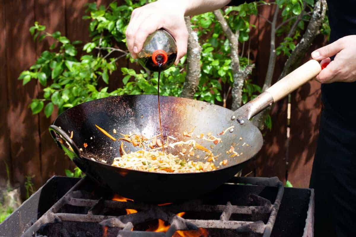 Soy sauce being poured onto a stir fry, in a wok on a grill