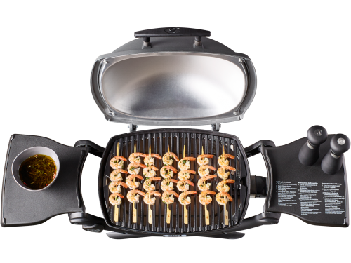 Weber Q2200 tabletop grill from above, with kebobs on the grill and sauce on the side table