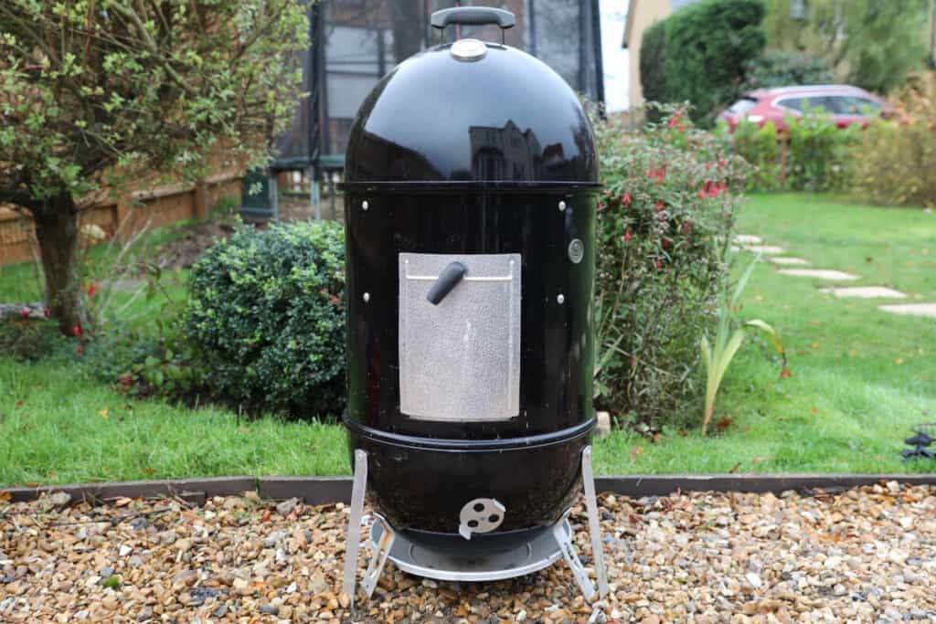 Weber Smokey Mountain smoker in a garden on a gravel path