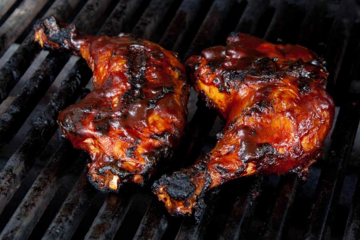 Chicken leg quarters on a bbq grill, coated in sauce