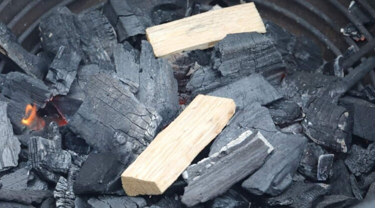 2 chunks of smoking wood on a bed of charcoal