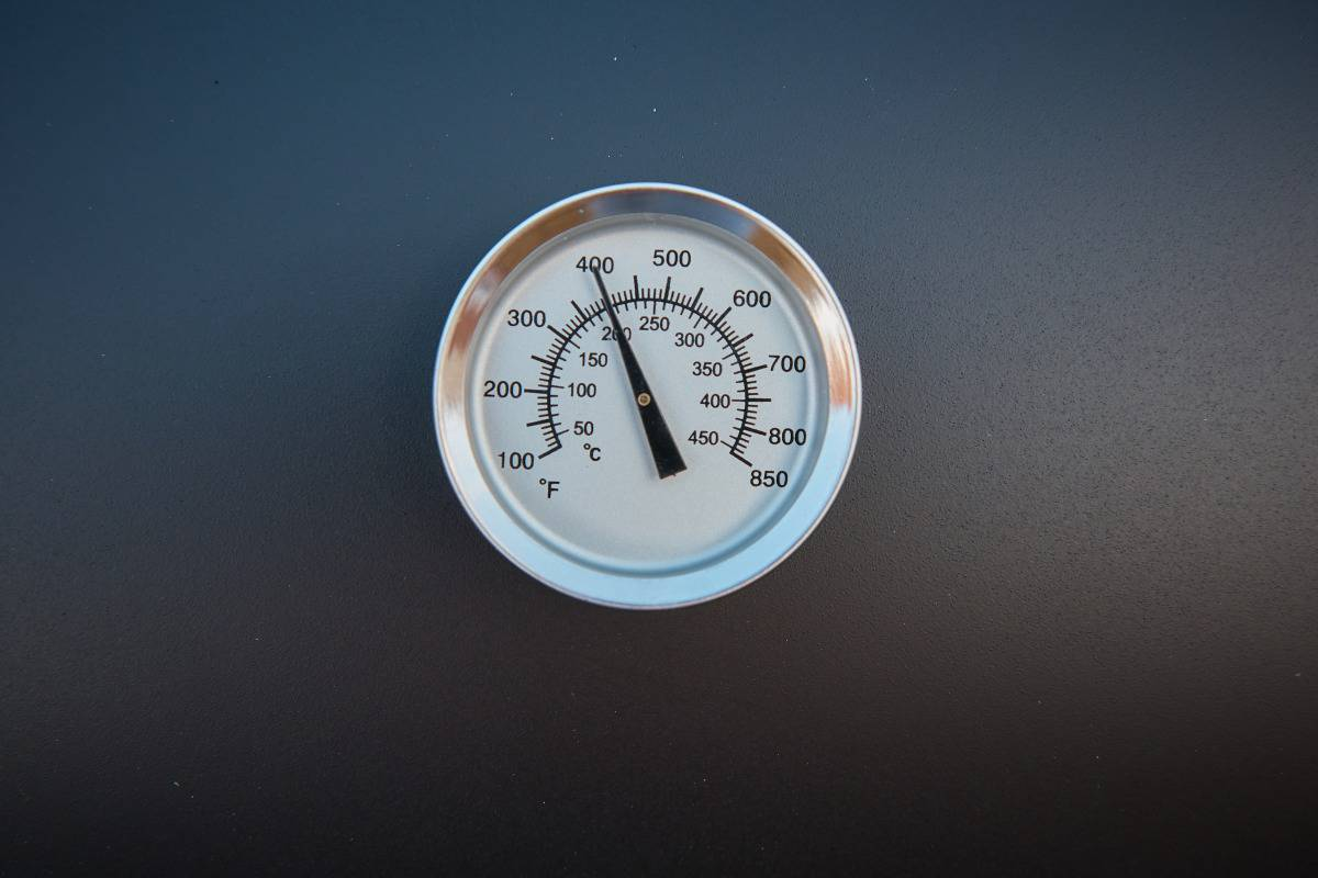A grill lid thermometer with a black background
