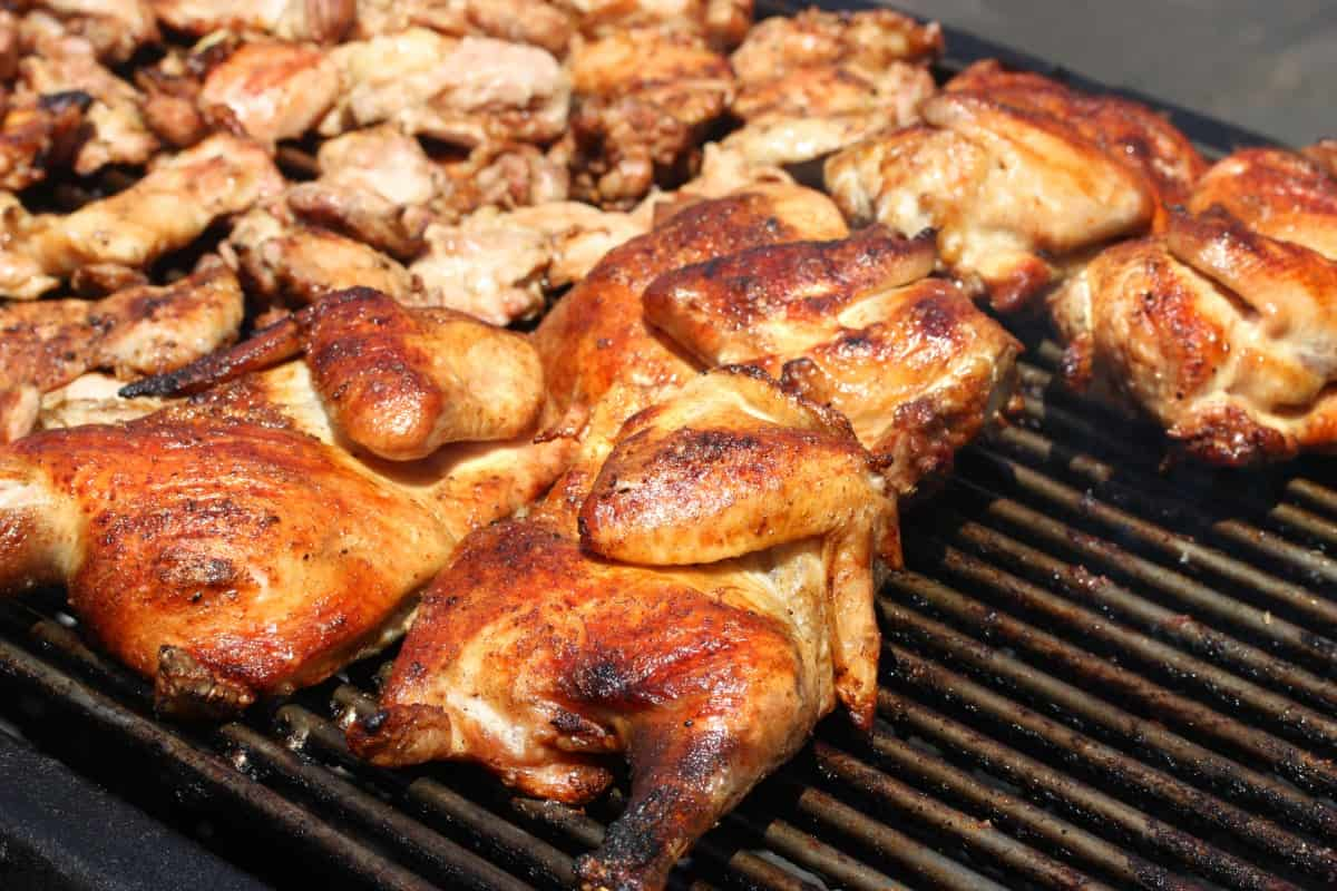 Different cuts of chicken on an open grill