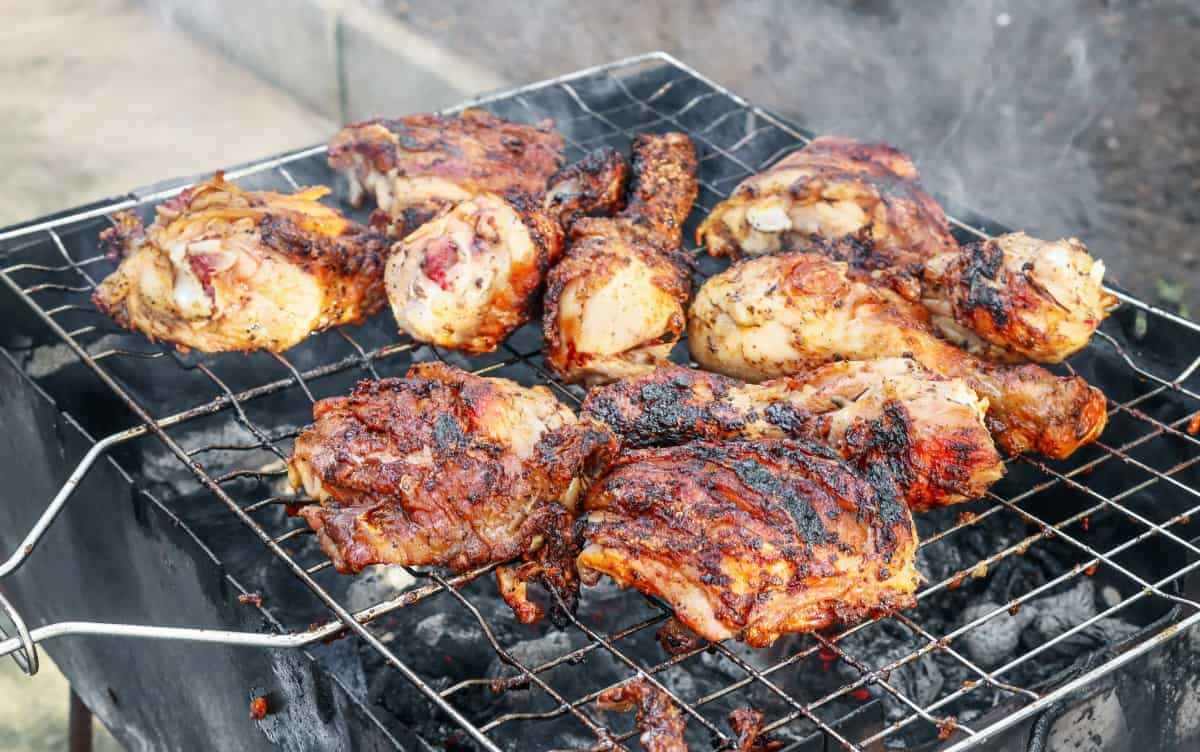 Grilling chicken thighs and drumsticks on an open charcoal grill