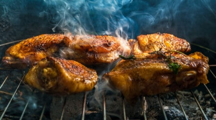 Chicken pieces smoking on a grill