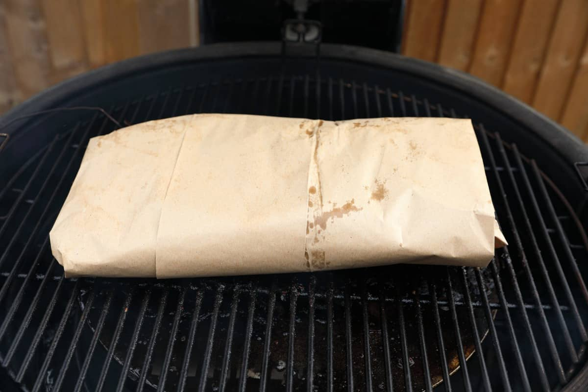 A pink butcher paper wrapped brisket on a kamado style smoker