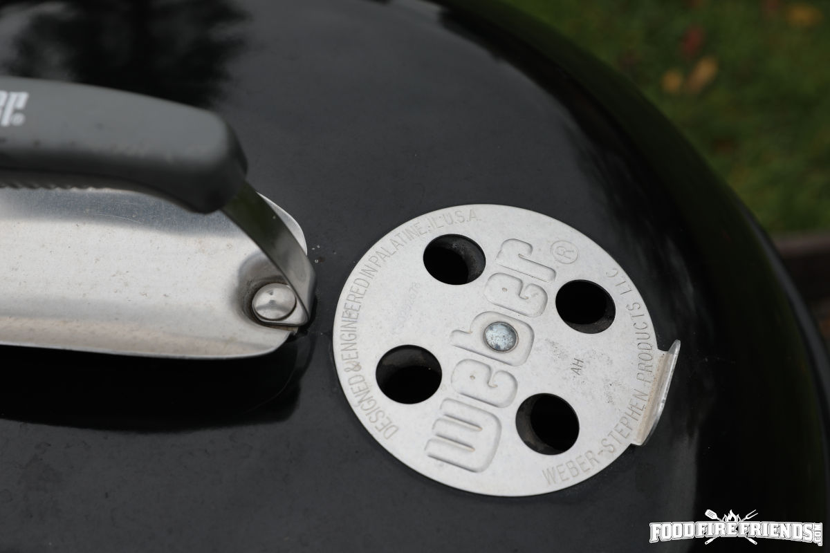 Close up of weber kettle top vent, handle and heat shield