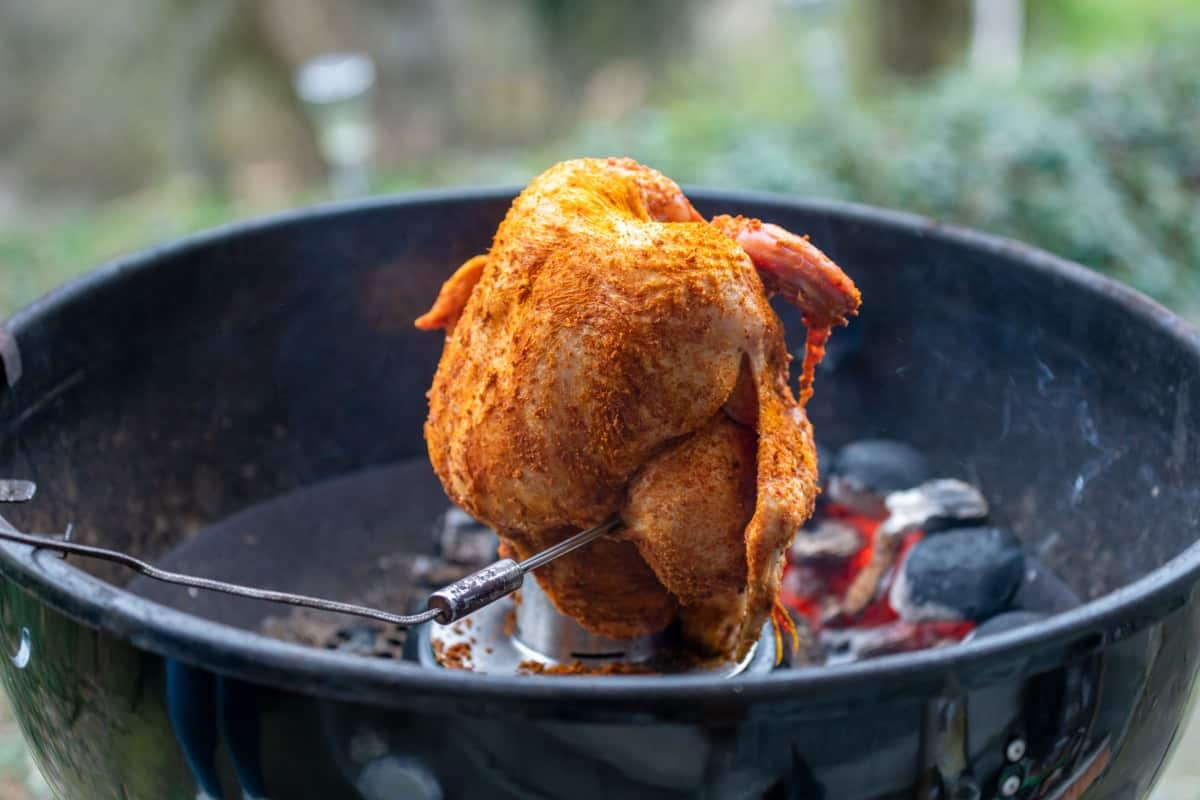 Whole chicken being grilled 'beer can style' on an open grill