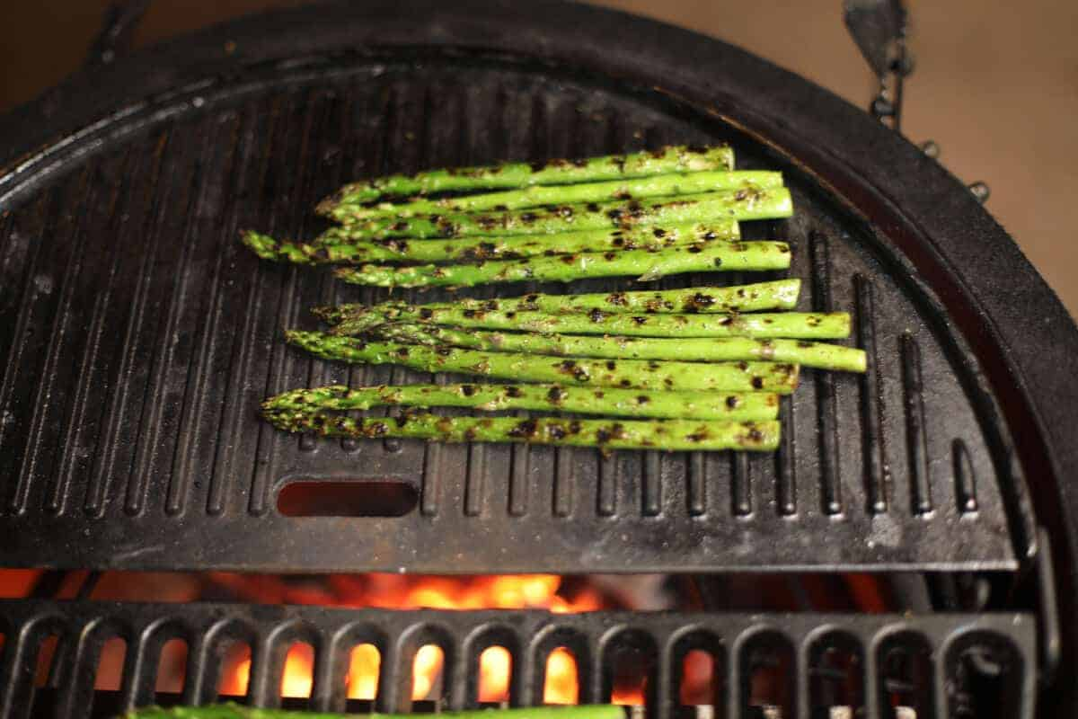 Asparagus on a solid cast iron grate on a charcoal grill