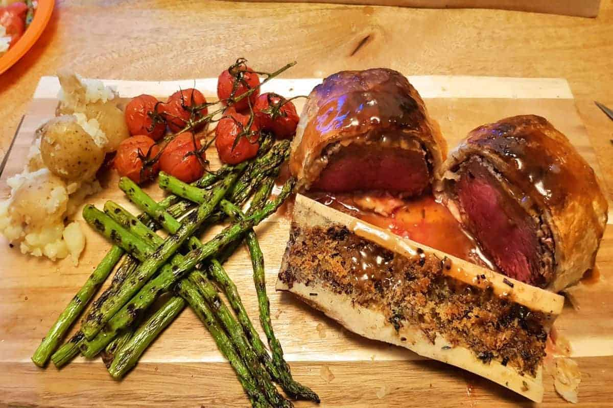 Beef wellington, bone marrow canoe and roasted veg on a wooden chopping board