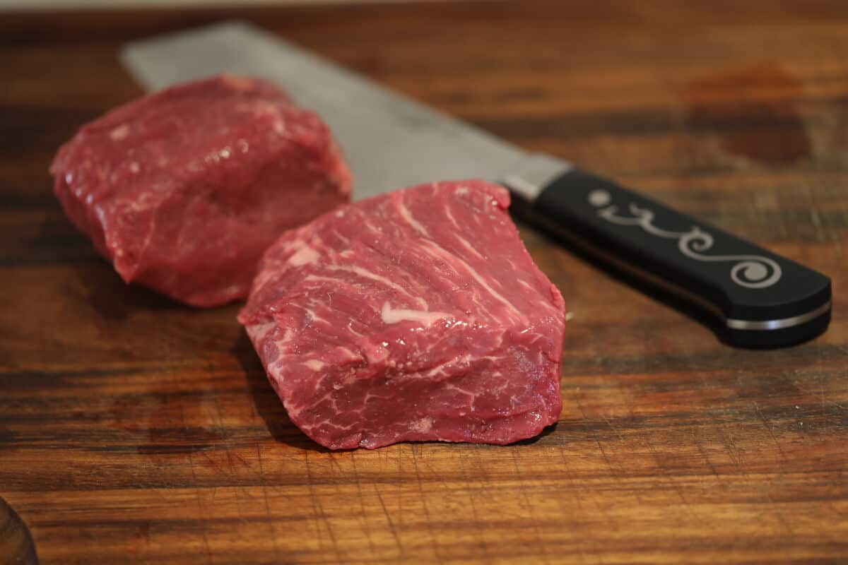 two pieces of Basque beef filet and a japanese knife on a chopping board