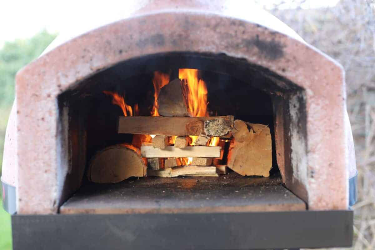 Wood fired oven with varying sized wood on fire just inside