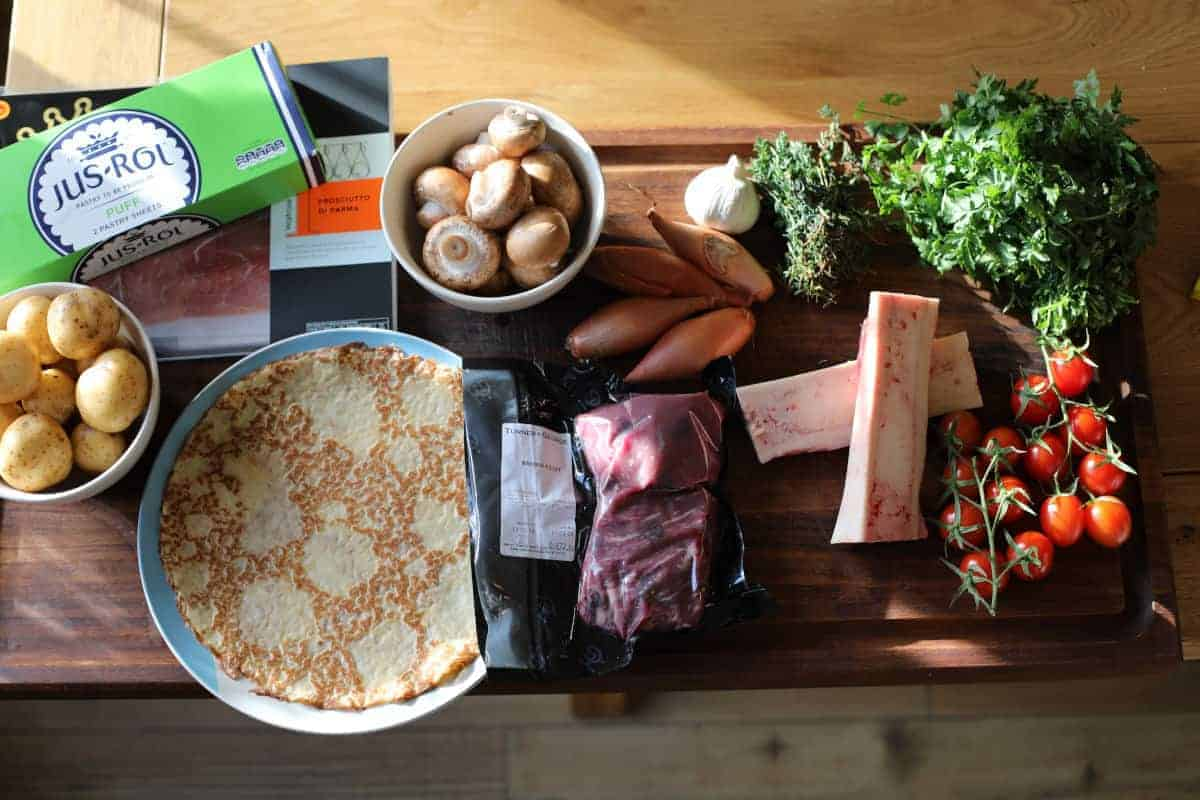 Most of the ingredients required for a beef wellington, laid out on a wooden chopping board